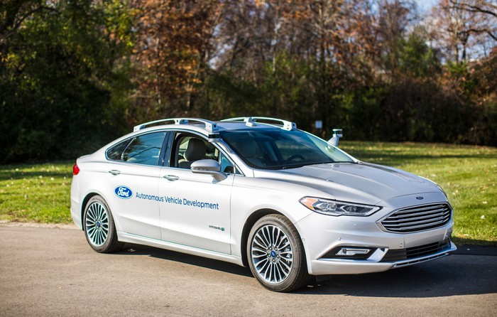 A white Ford Fusion equipped with a prototype self-driving system is shown parked near a field.