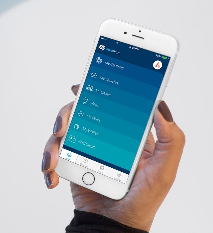 A hand holding a white iPhone showing the FordPass app's menu screen.