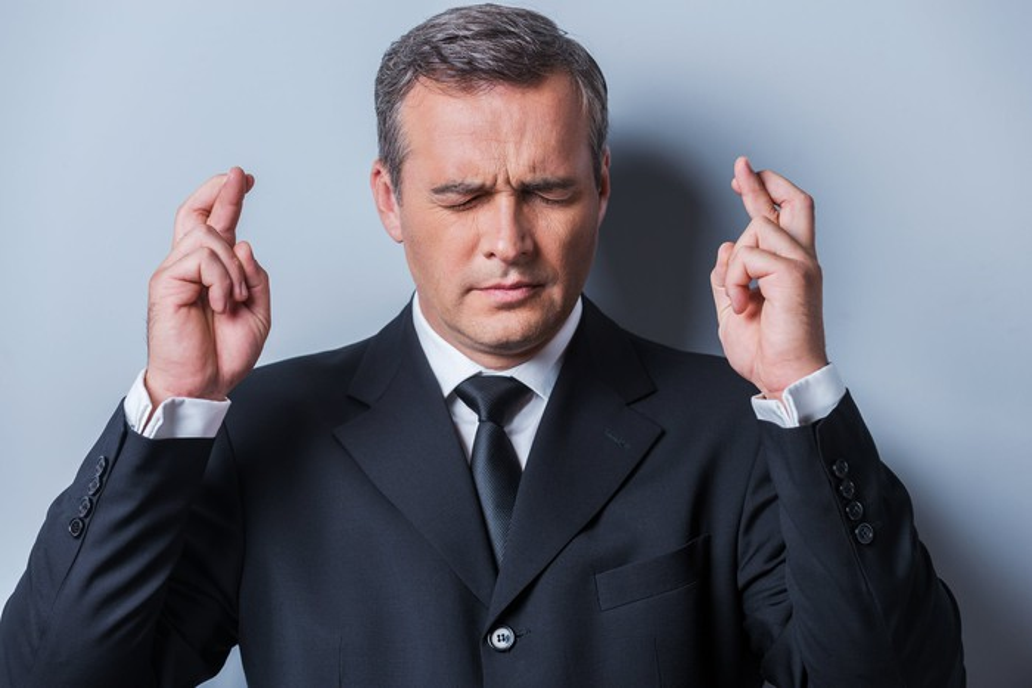 Businessman crossing his fingers.