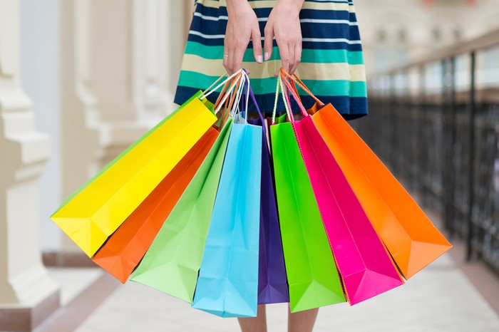 A woman holding colorful shopping bags.