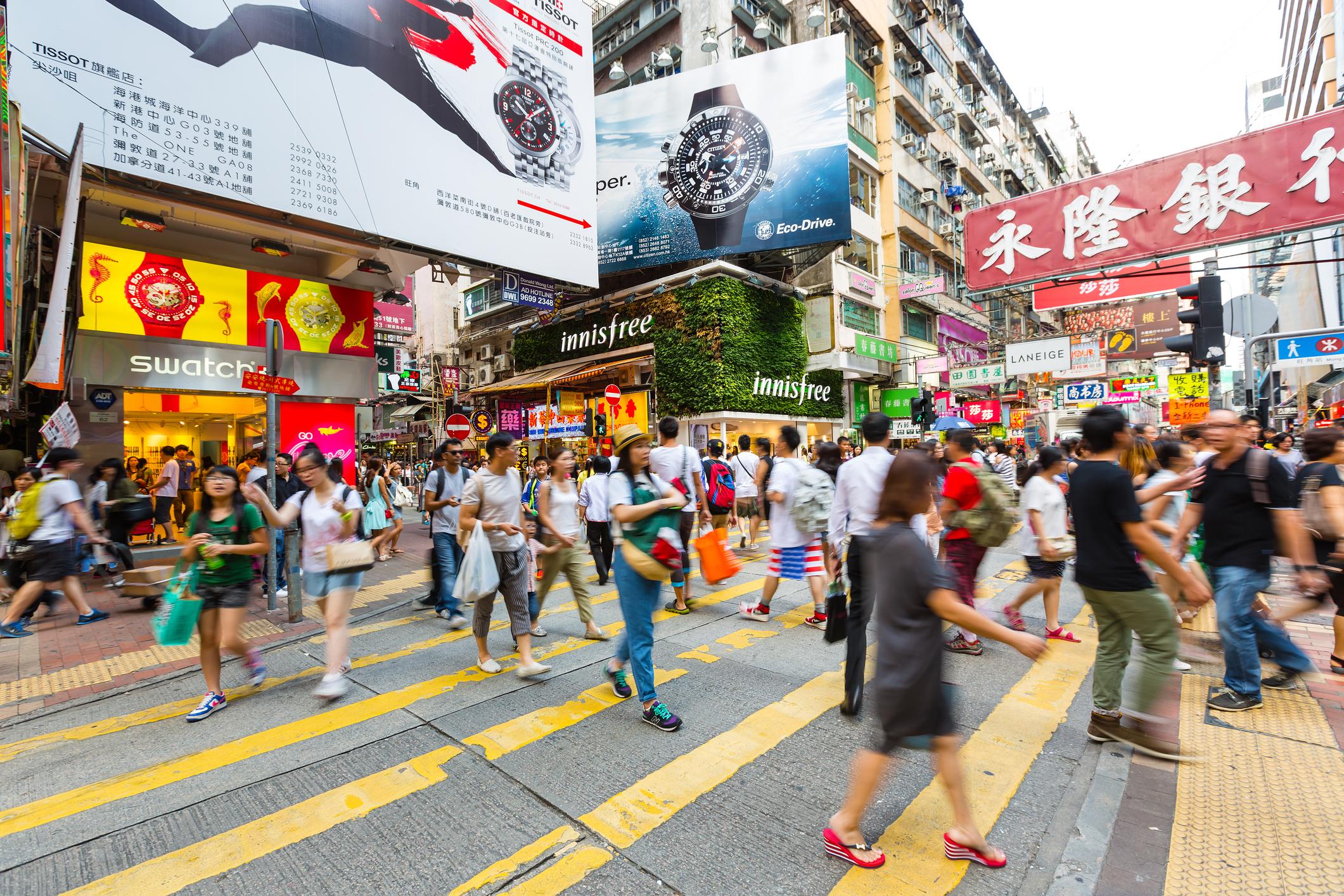 Pedestrians walking on a busy Hong Kong street.