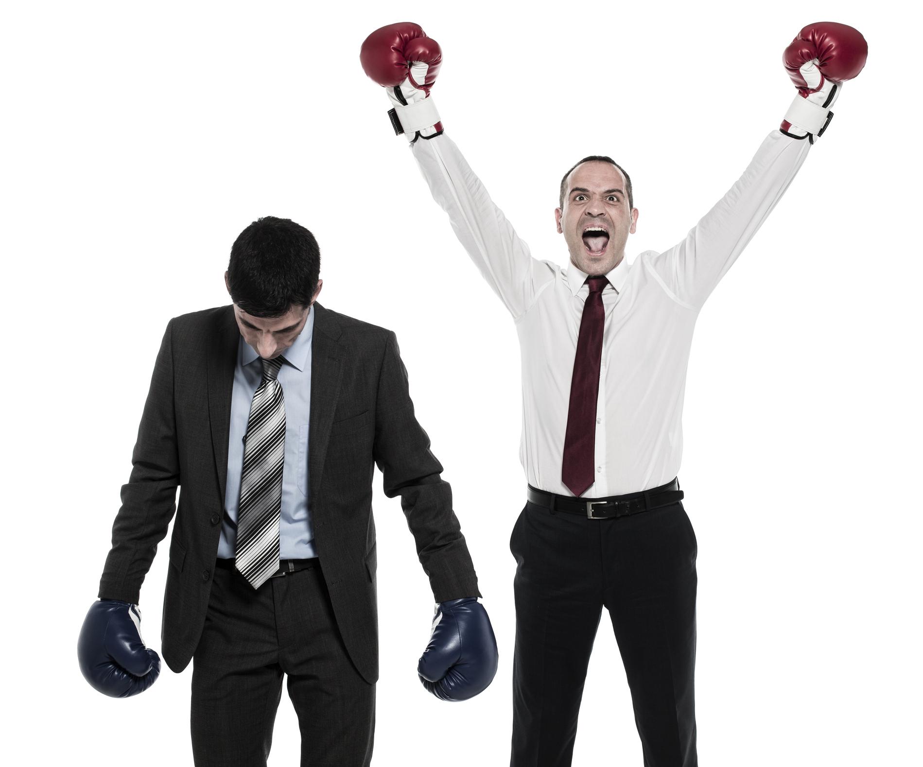 Businessmen wearing boxing gloves.