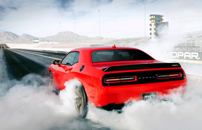A red Dodge Challenger SRT Hellcat burning rubber on a drag strip.