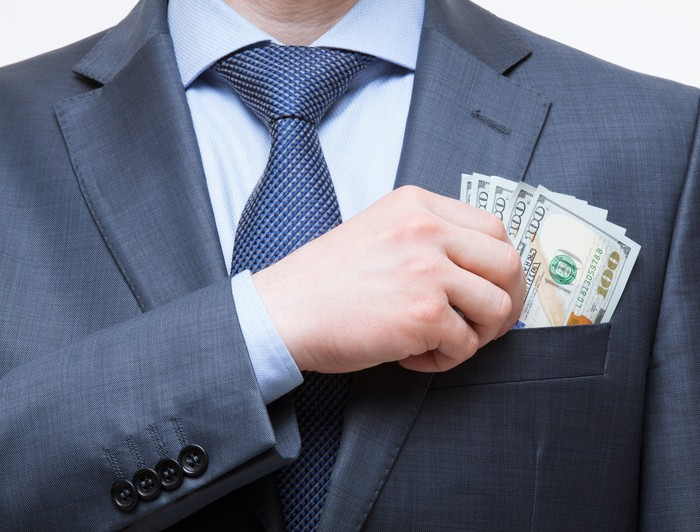 Wealthy businessman putting cash in his front pocket.