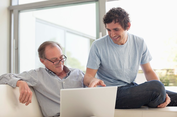 Father and son looking at laptop screen and having a discussion.