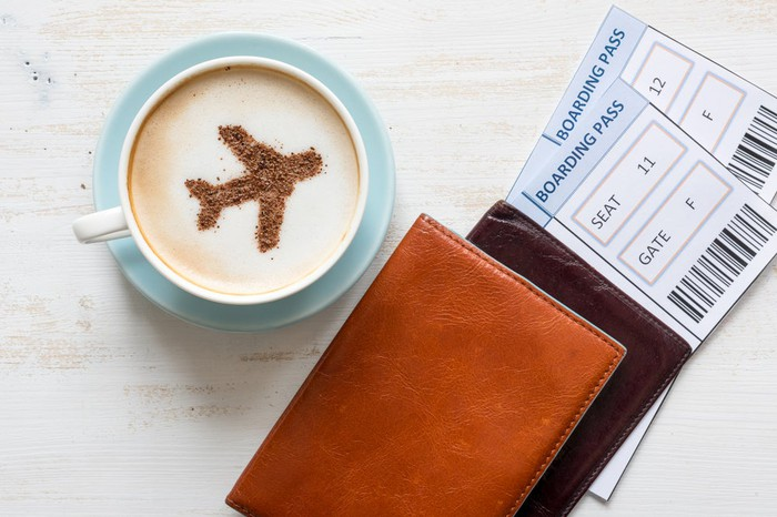Cappucino cup with airplane art in foam, boarding passes.