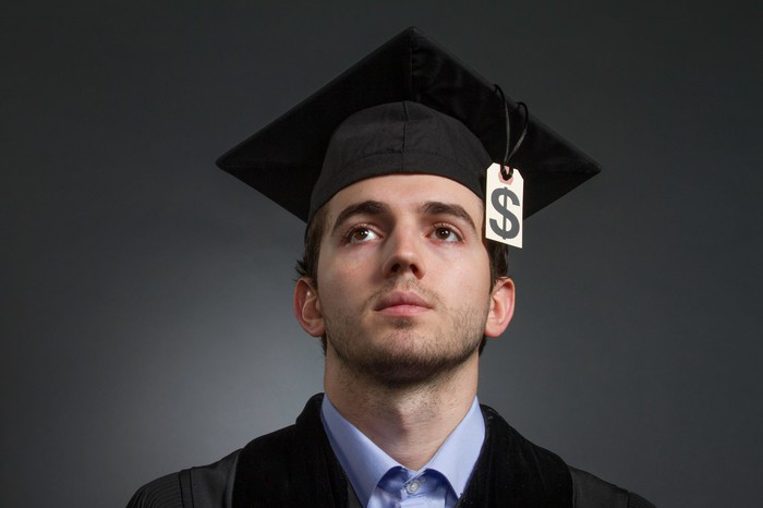 College student wearing a cap and gown with a dollar sign at the end of the tassel.