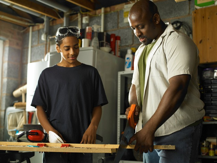Father teaching his teenage son about carpentry.
