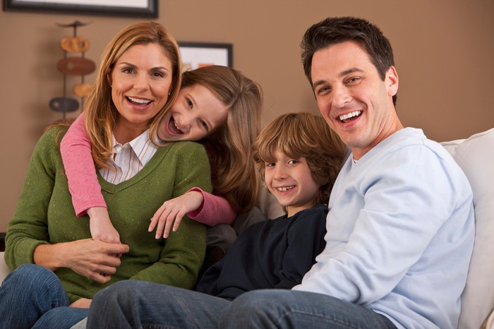 A smiling family portrait with both parents and two kids.