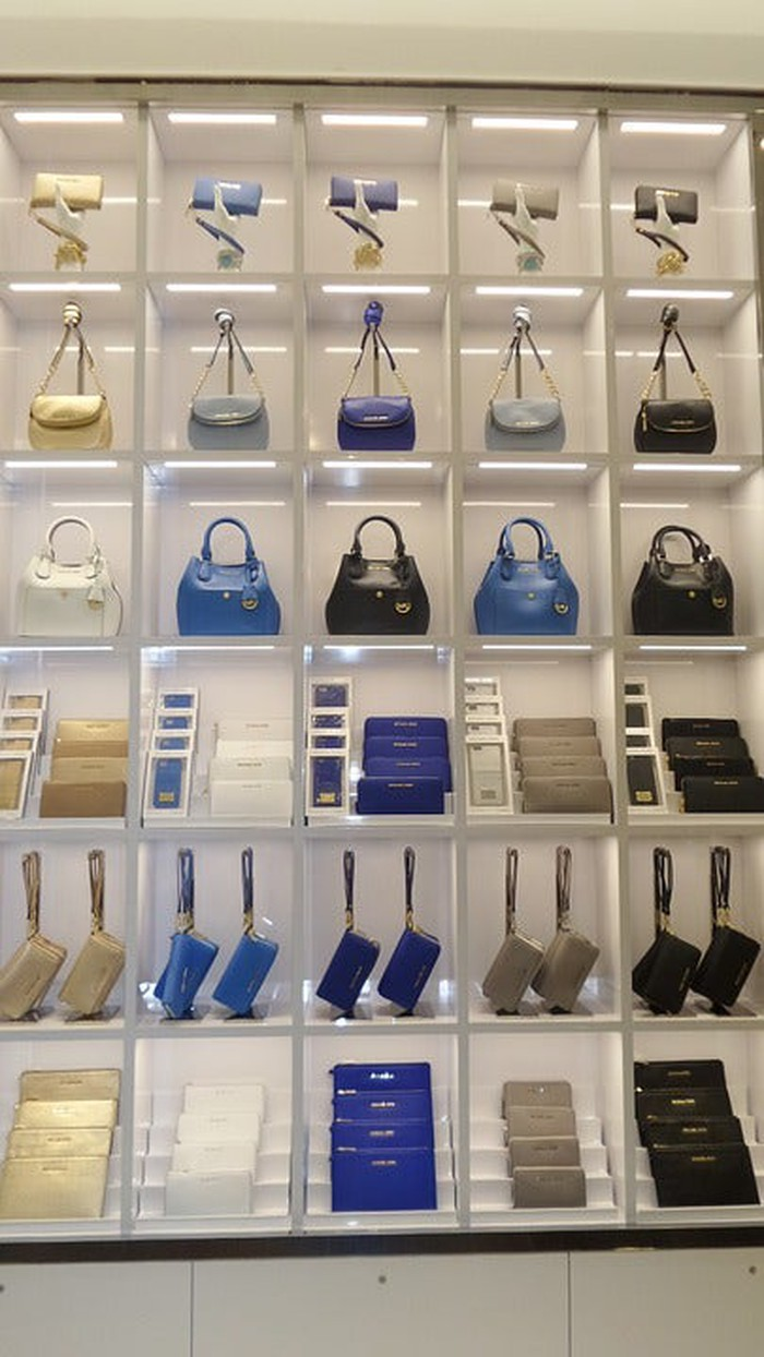 Purse rack in store featuring Michael Kors' products