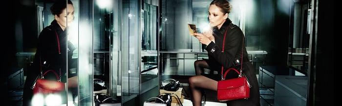 Woman putting on makeup while wearing Michael Kors apparel