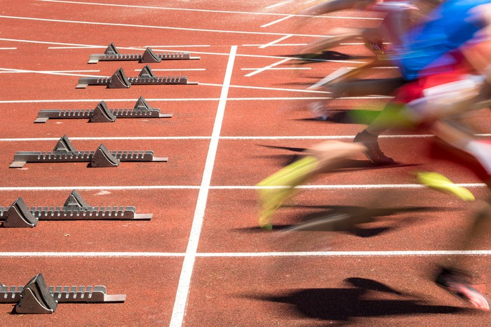 Picture of several runners leaving the starting blocks at a track race.