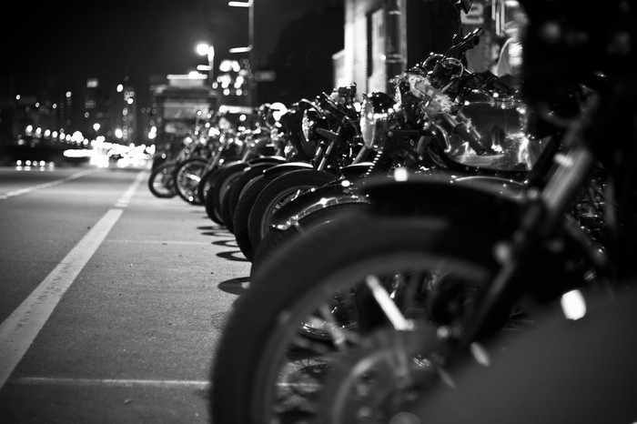 Black & white photo of motorcycles lined up on a street at night