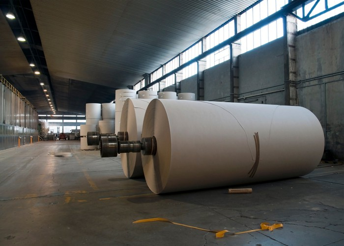 A roll of newly manufactured paper sitting on the floor of an industrial pulp and paper mill.
