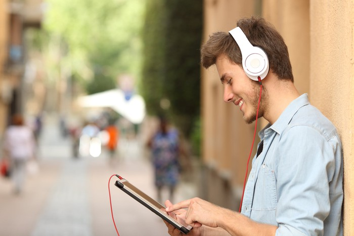 Young man watching his tablet with headphones on.