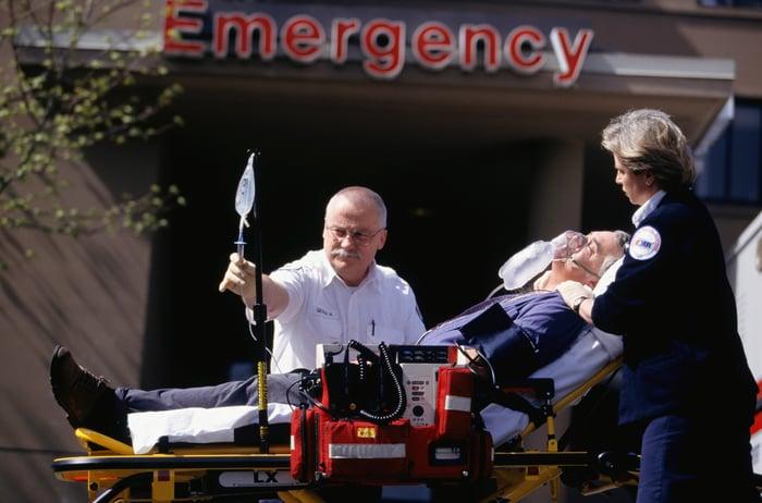 Healthcare worker transporting patient in emergency room