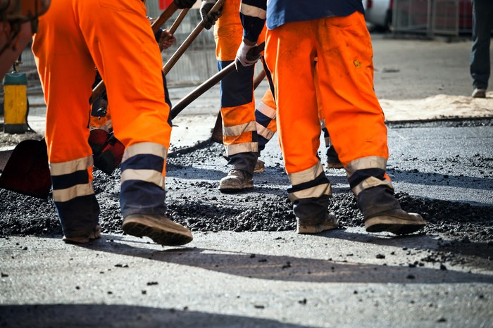 Road workers tearing up road
