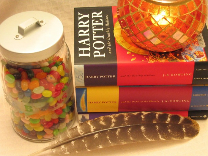 Two fat Harry Potter books stacked, next to candle, feather, and jar of jelly beans
