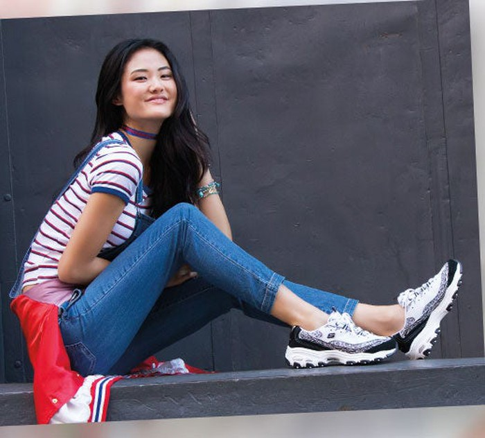 A young woman wearing Skechers sneakers.