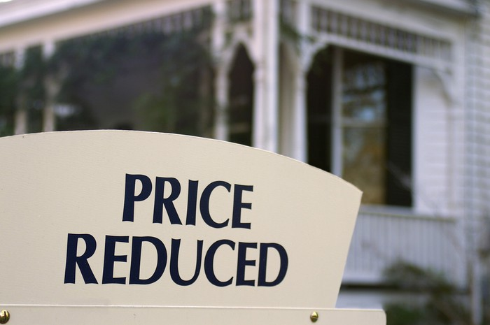 Home for sale with price reduced sign.