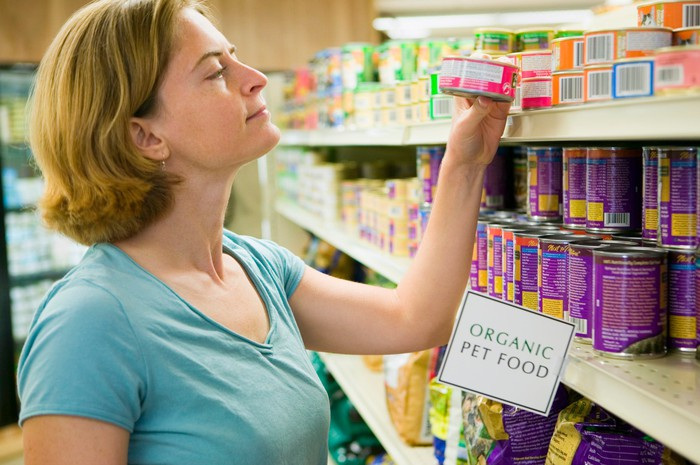 A woman shopping for pet food.