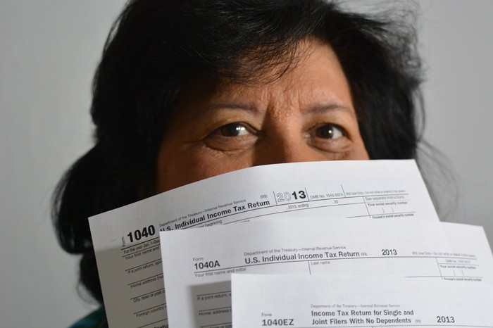 Woman holding tax returns partially concealing her face.