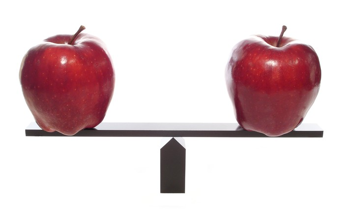 Picture of two apples on a scale that balance each other out.