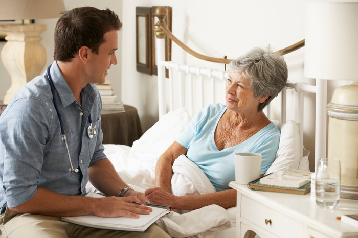 Doctor talking with senior patient in bed
