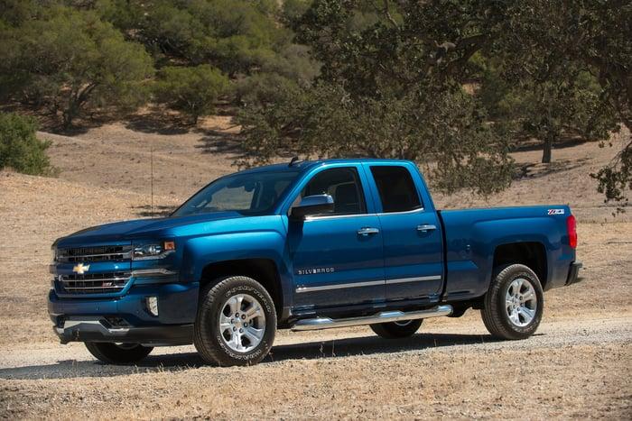 A blue 2017 Chevrolet Silverado 1500 pickup on a country road.