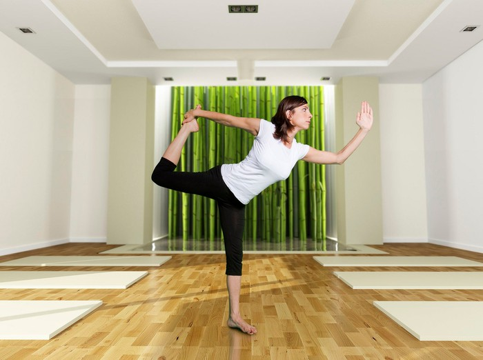 Woman stands in a yoga pose on hardwood floor.