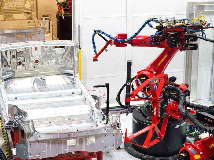 A Tesla vehicle in an early stage of production on the robotic assembly line