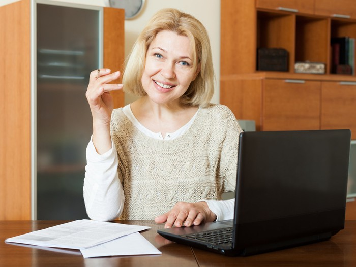 A smiling woman examining financial documents.