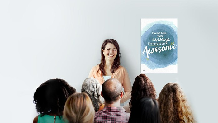 """A smiling woman speaking to a group of Weight Watchers meeting participants in front of a sign that reads """"I'm not here to be average, I'm here to be awesome."""""""