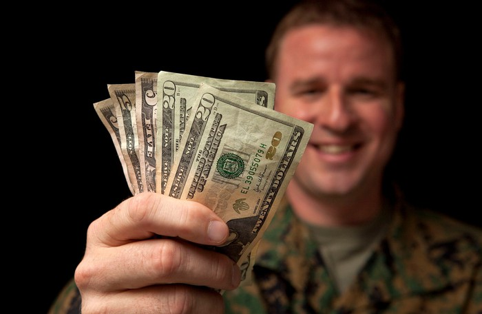 Military servicemember with handful of money