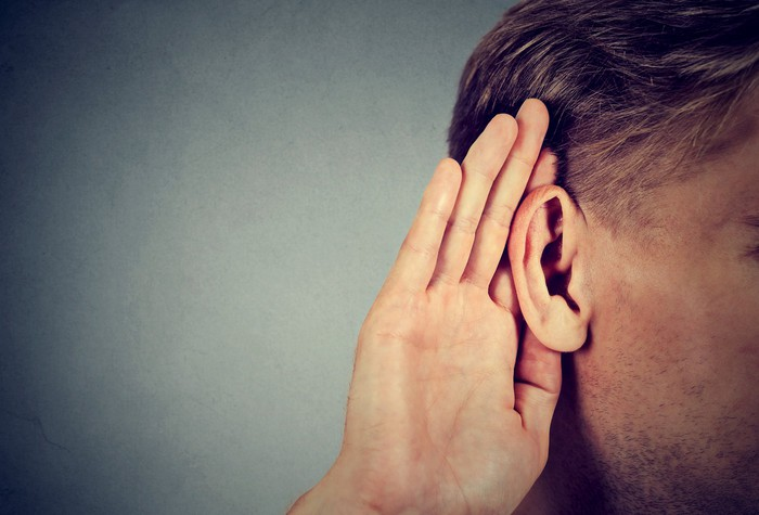 A man cups his ear as if ready to hear something.