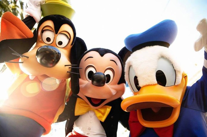 Goofy, Mickey Mouse, and Donald Duck posing for a photo at Disneyland.