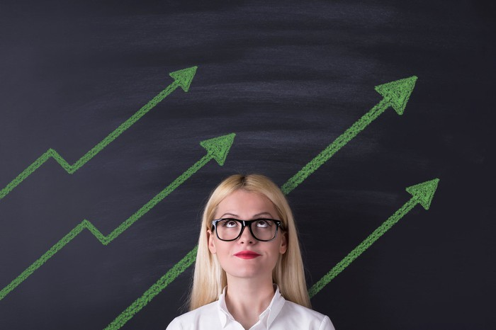 Woman looking up in front of upward sloping arrows drawn on a chalkboard