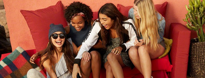 A group of young women laughing on a couch in a Hollister clothing ad.