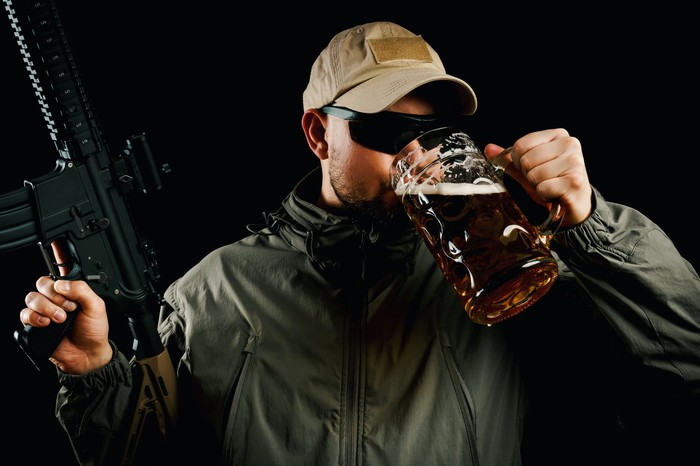 Man drinking from large mug of beer while holding a modern sporting rifle