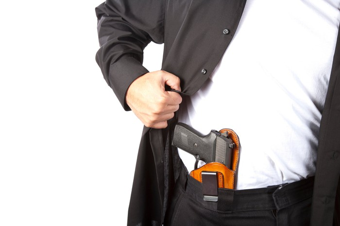 Man in suit revealing a holstered gun in his waistband