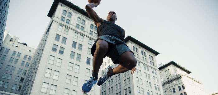 A basketball player wearing Nike shoes jumps over the camera about to dunk the ball.