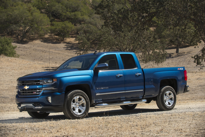 A blue 2017 Chevrolet Silverado pickup on a dirt road.
