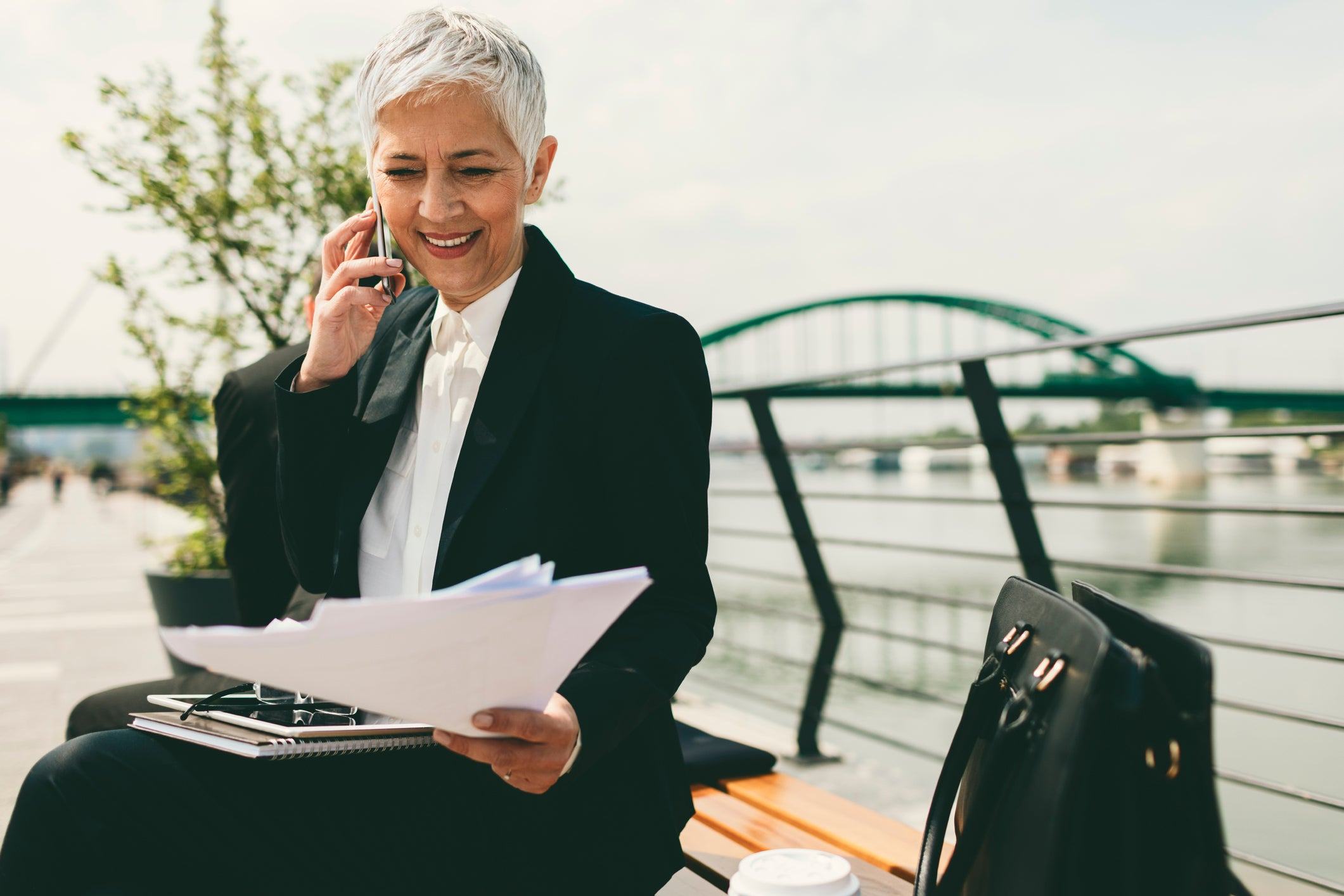 Middle-aged businesswoman sitting on a bench and talking on a cellphone