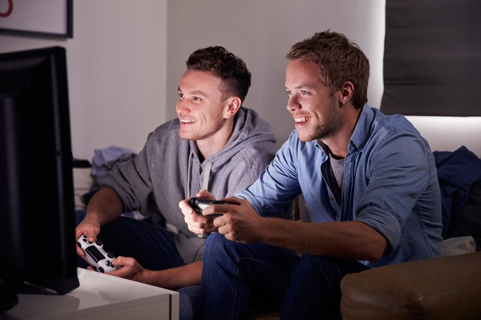 Two guys sitting on a couch playing video games.