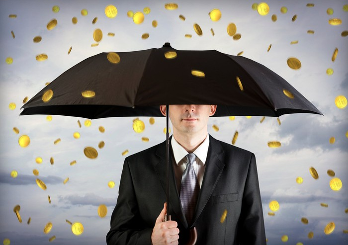 Man in suit holding an umbrella as gold coins fall out of the sky.
