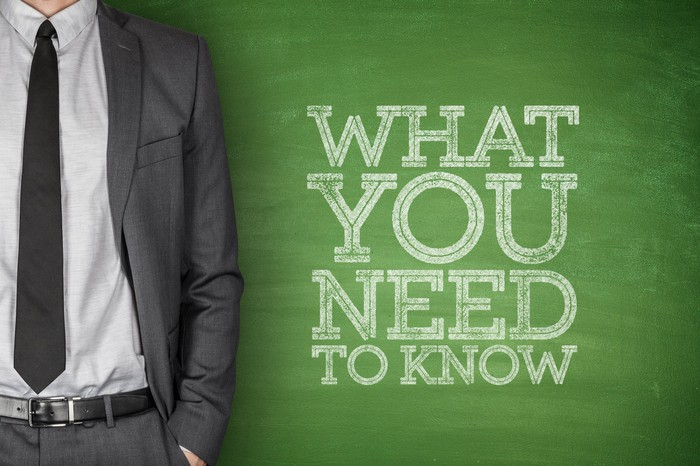 """""""what you need to know"""" written on chalkboard, with torso shown of man in suit next to it"""