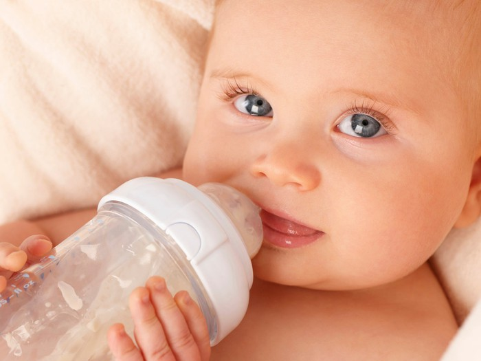 Close-up of an infant drinking from a bottle.
