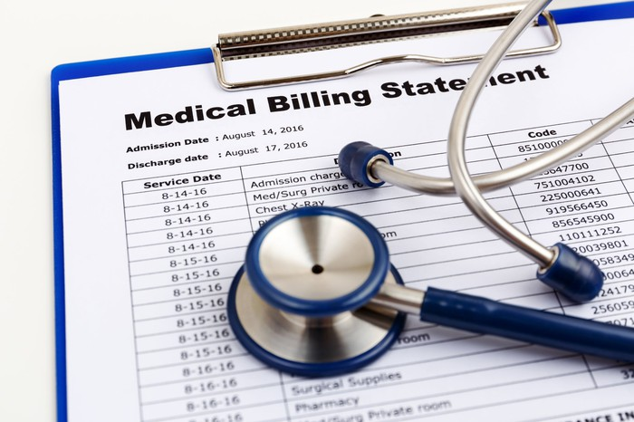 Stethoscope sitting atop a large medical bill.
