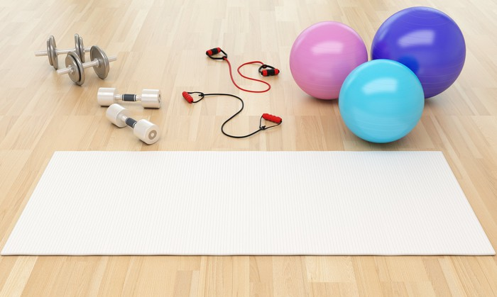 A grouping of exercise equipment in a gym, including a yoga mat and barbells
