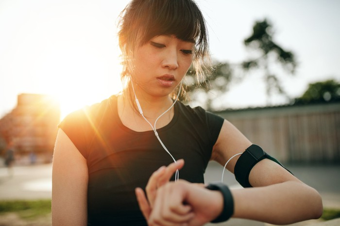 A woman uses her fitness wearable during a workout.